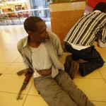 An injured policeman holds on to his wound as his compatriot searches through a shopping centre for gunmen in Nairobi