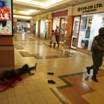 A soldier walks past a body as people hug each other leaving Westgate shopping centre, after gunmen went on a shooting spree, in Nairobi