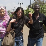 An injured woman is helped out of the Westgate Shopping Centre where gunmen went on a shooting spree, in Nairobi