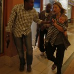 Armed police guide a woman carrying a child to safety at Westgate Shopping Centre in Nairobi