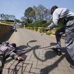 Armed police approach the entrance of Westgate Shopping Centre, past a body, in Nairobi
