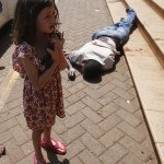 A girl stands by the body of a man after escaping Westgate Shopping Centre in Nairobi