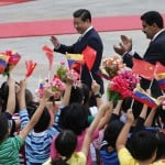 Venezuela's President Nicolas Maduro and Chinese President Xi Jinping respond to children waving the national flags from both countries in Beijing