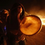 A participant makes her way around the flames during the Burning Man 2013 arts and music festival in the Black Rock Desert of Nevada