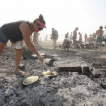 Rhonda Clark cooks hash browns for breakfast on the burned remains of the Man during the Burning Man 2013 arts and music festival in the Black Rock Desert of Nevada
