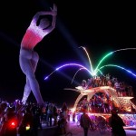 """Participants dance around and atop an art car parked beside the """"Truth is Beauty"""" sculpture created by Marco Cochrane at the 2013 Burning Man arts and music festival in the Black Rock desert of Nevada"""
