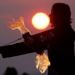 Krissy Humphreys performs with fire at sunrise at the Temple of Whollyness during the Burning Man 2013 arts and music festival in the Black Rock Desert of Nevada