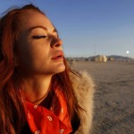 Alexandra Aguilera basks in the light of the rising sun at the 2013 Burning Man arts and music festival in the Black Rock desert of Nevada