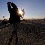 "Rochelle Schieck dances by the ""Truth is Beauty"" sculpture at the 2013 Burning Man arts and music festival in the Black Rock desert of Nevada"