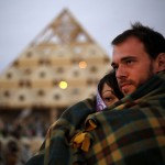 Katherine Cadger and Kevin Rae watch the sunrise at the Temple of Whollyness during the Burning Man 2013 arts and music festival in the Black Rock Desert of Nevada