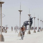 A participant bicycles away from the effigy of the Man at the 2013 Burning Man arts and music festival in the Black Rock Desert of Nevada
