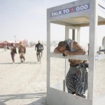 Pippin, his Playa name, chats on the phone with God during the Burning Man 2013 arts and music festival in the Black Rock Desert of Nevada