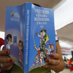 A child reads new edition of Venezuela's constitution, which displays image of late country's president Chavez on cover, in Caracas