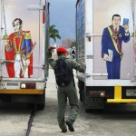 A soldier walks past truck painted with images of country's late president Chavez and independence hero Bolivar to distributed new edition of Venezuela's constitution in Caracas