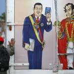 A soldier walks past truck painted with images of country's late president Chavez and independence hero Bolivar, distributing new editions of Venezuela's constitution in Caracas