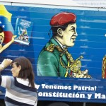 A woman walks past truck, painted with image of country's late president Chavez and independence hero Bolivar, as it distributes new edition of Venezuela's constitution in Caracas