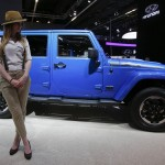 A model poses next to a Jeep Wrangler Unlimited during a media preview day at the Frankfurt Motor Show
