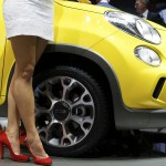 A model poses next to Fiat 500 L Trekking car during a media preview day at the Frankfurt Motor Show