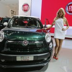 A model poses next to Fiat 500 L Living car during a media preview day at the Frankfurt Motor Show