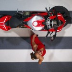 A model is reflected in a mirror as she poses with a Ducati motorcycle during a media preview day at the Frankfurt Motor Show