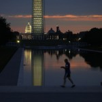 An early morning jogger is pictured at the Lincoln Memorial reflecting pool at sunrise in Washington