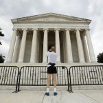 Barricades close off the Jefferson Memorial as a jogger stops to take a photo in Washington