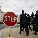Visitors walk past a stop sign on the Senate side of the U.S. Capitol in Washington