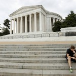 Barricades close off the Jefferson Memorial as a jogger sits on its steps in Washington