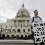 Furloughed federal employee holds sign on the steps to the U.S. Capitol after the U.S. Government shut down last night, on Capitol Hill in Washington