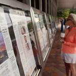 Two women read morning newspapers from around the United States at the Newseum in Washington