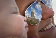 The Statue of Liberty is reflected in the glasses of Katie Ullman as she points to it while she holds her son Tyler in her arms on Liberty Island in New York