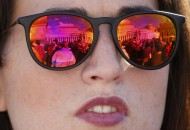 St.Peter's square is reflected in sunglasses of a faithful during Pope Francis' Sunday prayer in St. Peter's square at the Vatican