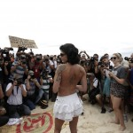 Media members surround a woman as she takes off her top as a protest, at Ipanema beach in Rio de Janeiro