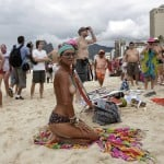 A woman kneels with her top off as a protest, at Ipanema beach in Rio de Janeiro