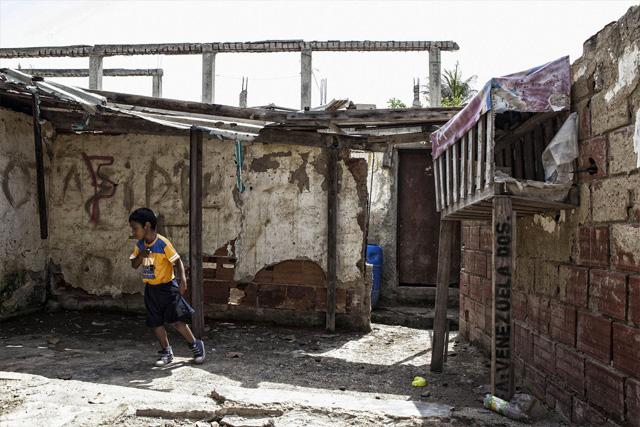 Cinco familias comparten una casa precaria mientras esperan una vivienda nueva a escasos metros / Foto Bloomberg