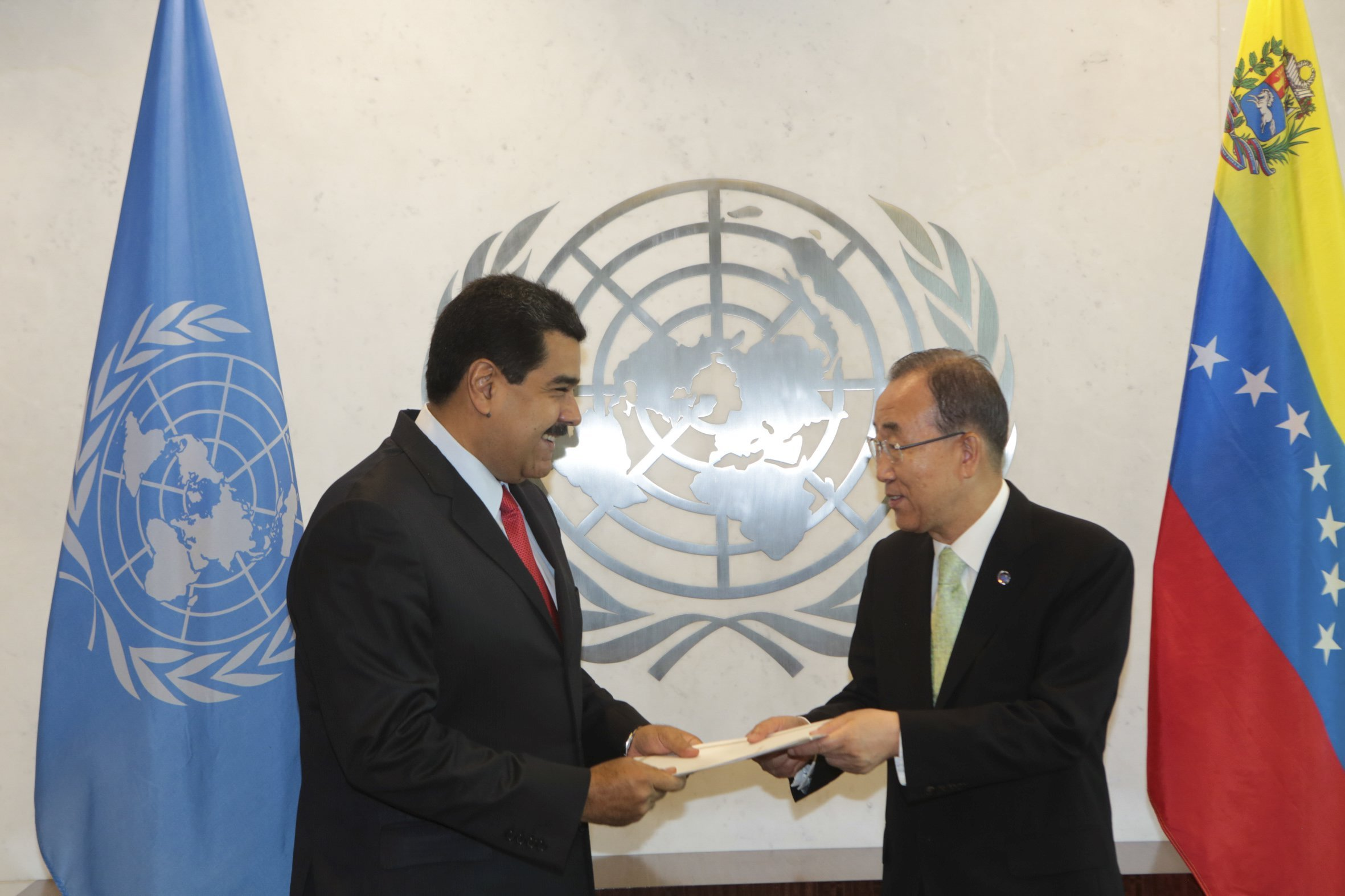 U.N. Secretary-General Ban Ki-moon (R) and Venezuela's President Nicolas Maduro, hold a document as they talk, during their meeting at the United Nations headquarters in New York