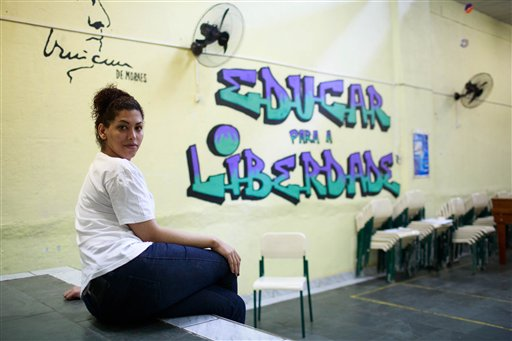 """En esta imagen del 8 de julio de 2015, la interna transexual Estefanie Ferraz posa para una fotografía junto a un mural que dice """"Educar para la libertad"""" en la prisión Evaristo de Moraes donde cumple sentencia en Río de Janeiro, en Brasil.  Los baños de sol, que suelen ser un momento de asueto de la vida en las sobrepobladas prisiones, eran una pesadilla para Ferraz. Después de afeitarle el pelo, uno de los guardas de un penal masculino la obligó a quitarse la camisa en el patio, exponiendo los pechos que se había implantado ante cientos de presos. (AP Foto/Mauro Pimentel)"""