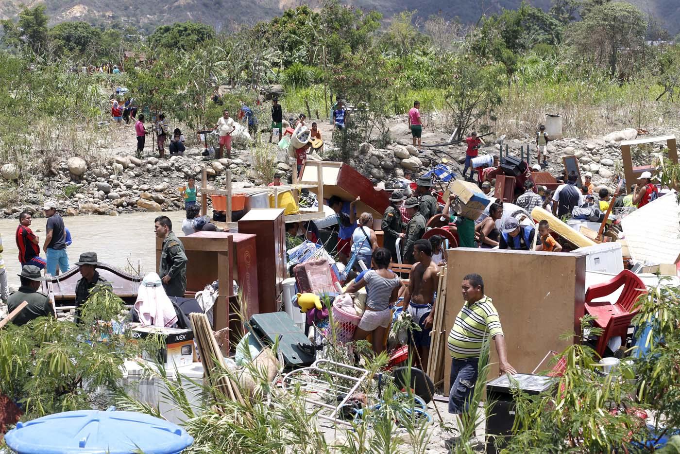 Personas llevan sus pertenencias mientras cruzan el río Táchira, que cruza Venezuela y Colombia, cerca de Villa del Rosario