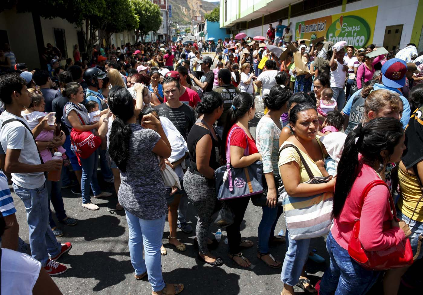 People queue outside a supermarket while trying to buy staple items close to the border with Colombia at San Antonio in Tachira state