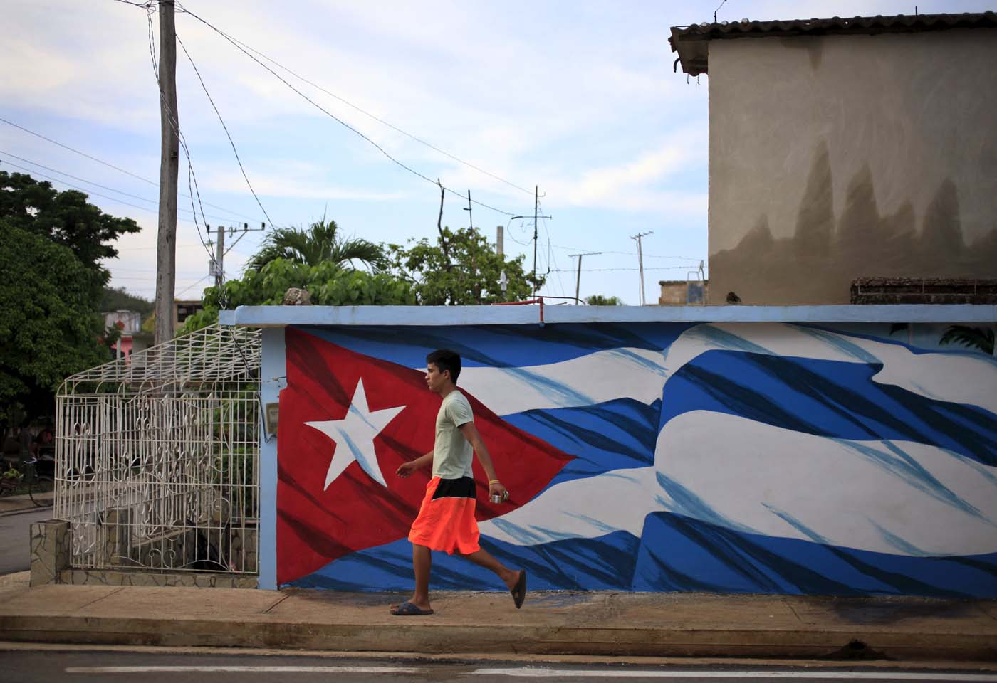 A man walks in front of a mural of the Cuban flag in Holguin, Cuba