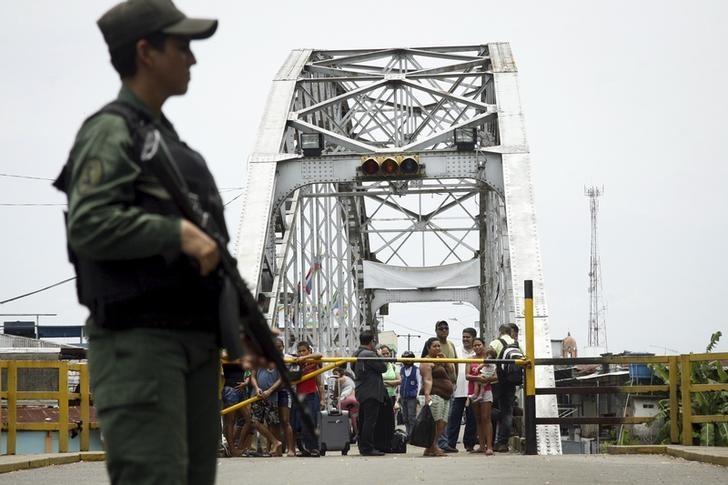Personas miran a un soldado venezolano que hace guardia en el puente internacional de La Unión, en la frontera entre Colombia y Venezuela, en el estado de Táchira, 29 de agosto de 2015. REUTERS/Carlos Eduardo Ramirez