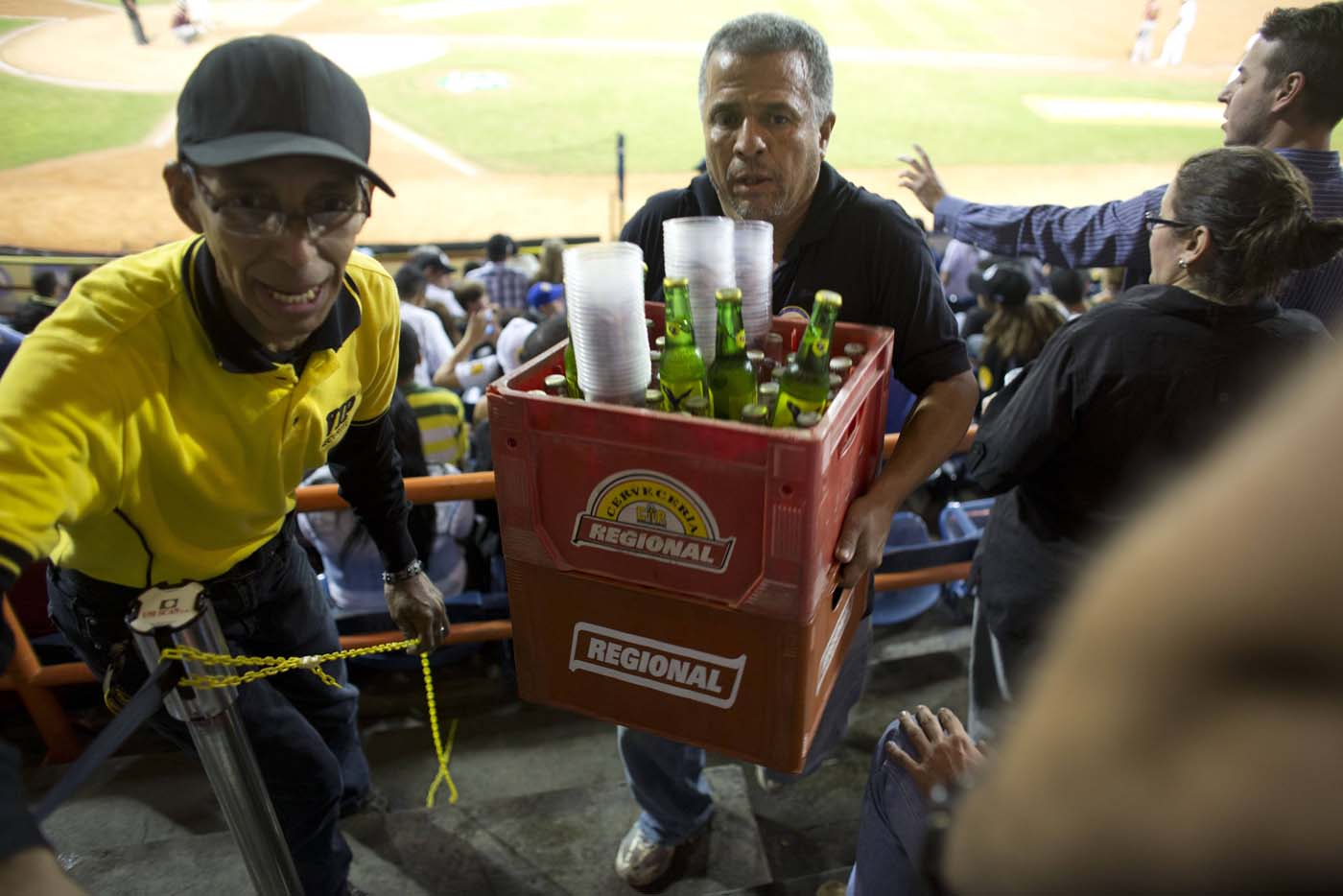 Un vendedor carga envases de cerveza durante un juego de béisbol entre los Leones de Caracas y los Navegantes de Magallanes en Caracas, Venezuela. Los aficionados no están contentos con la noticia de que el precio de la botella se incrementó de 30 a 120 bolívares en el último año, y las marcas más populares ya no están a la venta. (Foto AP/Ariana Cubillos)