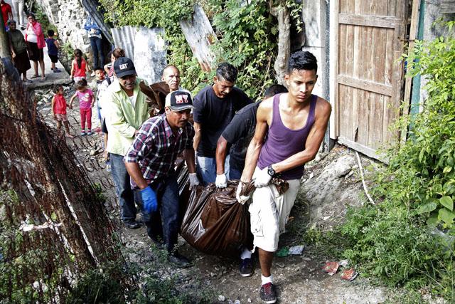 """Un grupo traslada los cuerpos de hombres que fueron asesinados por jóvenes armados tras ser sacados de sus casas en en una barriada de Tegucigalpa, Honduras, el miércoles 25 de noviembre de 2015. Siete personas fueron asesinadas a tiros en un barrio conocido como el """"Infiernito"""" en Tegucigalpa y ocho conductores de buses de pasajeros fueron asesinados en una estación de transporte en la ciudad de Choloma, próxima a San Pedro Sula en el norte del país del martes 24 de noviembre de 2015.(AP Photo/Fernando Antonio)"""