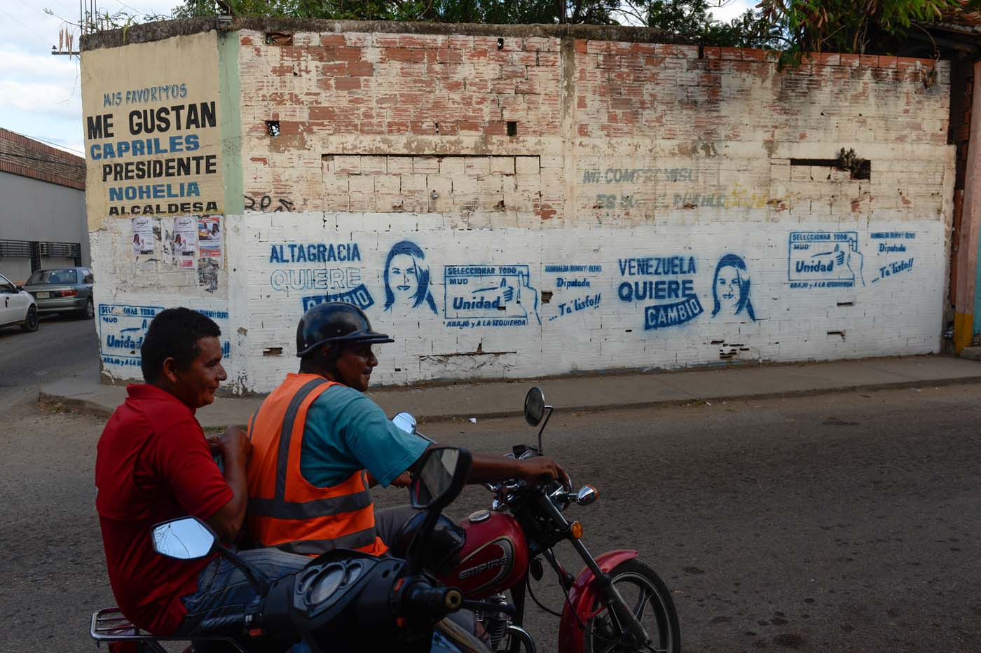 """A motorcyclist passes   by a graffiti depicting a Venezuelan opposition candidate for the upcoming legislative elections Rumualda Olivo in the Altagracia de Orituco town in Guarico state, Venezuela, on November 26, 2015. An opposition candidate in Venezuela's upcoming legislative elections was shot dead during an event Wednesday. """"Luis Manuel Diaz, local leader of the Democratic Action party in Altagracia de Orituco (Guarico state) has just been shot dead,"""" the party's chairman Henry Ramos Allup said on Twitter. AFP PHOTO/ FEDERICO PARRA / AFP / FEDERICO PARRA"""