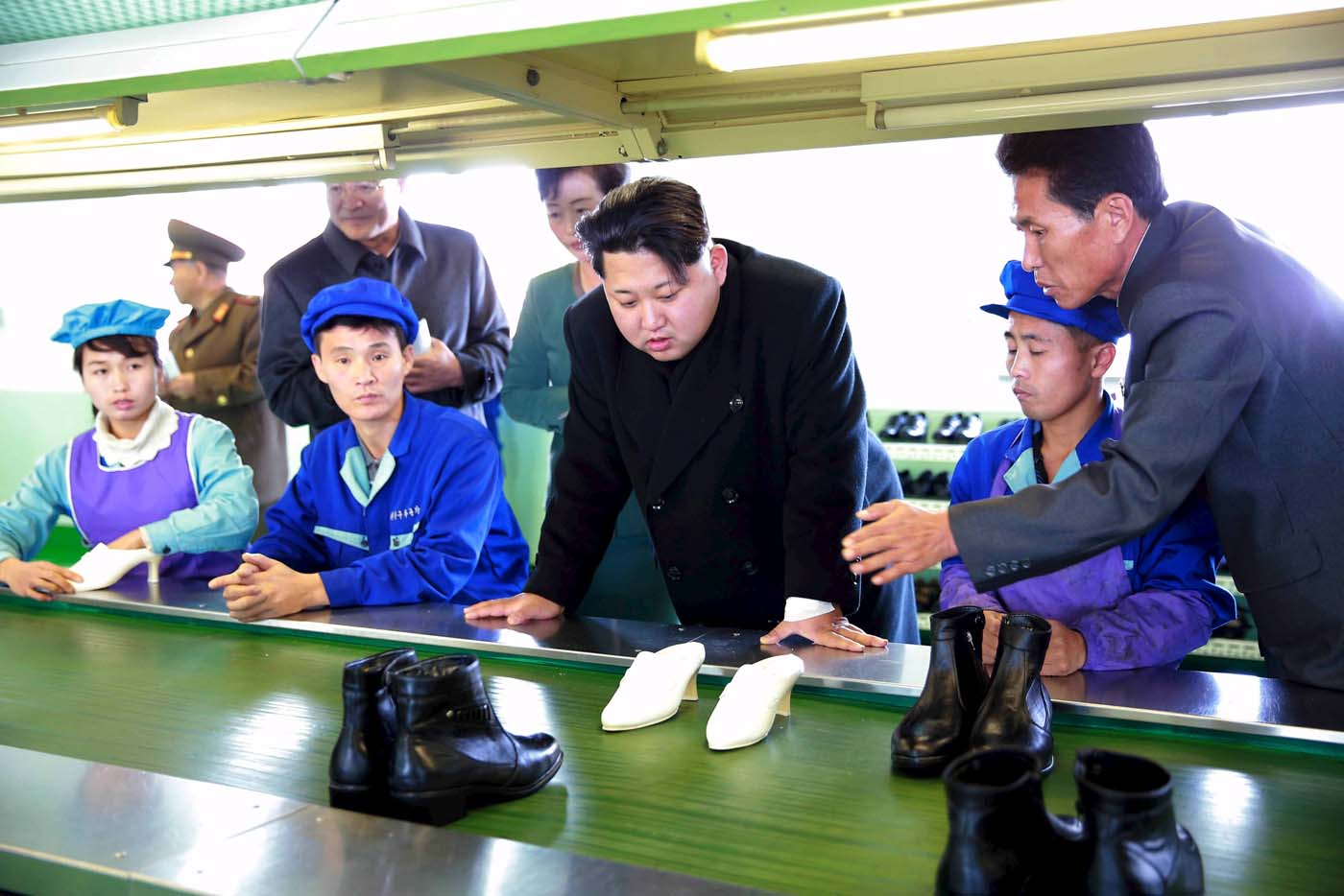 North Korean leader Kim Jong Un (3rd R) gives field guidance at the Wonsan Shoes Factory in this undated photo released by North Korea's Korean Central News Agency (KCNA) in Pyongyang November 27, 2015.