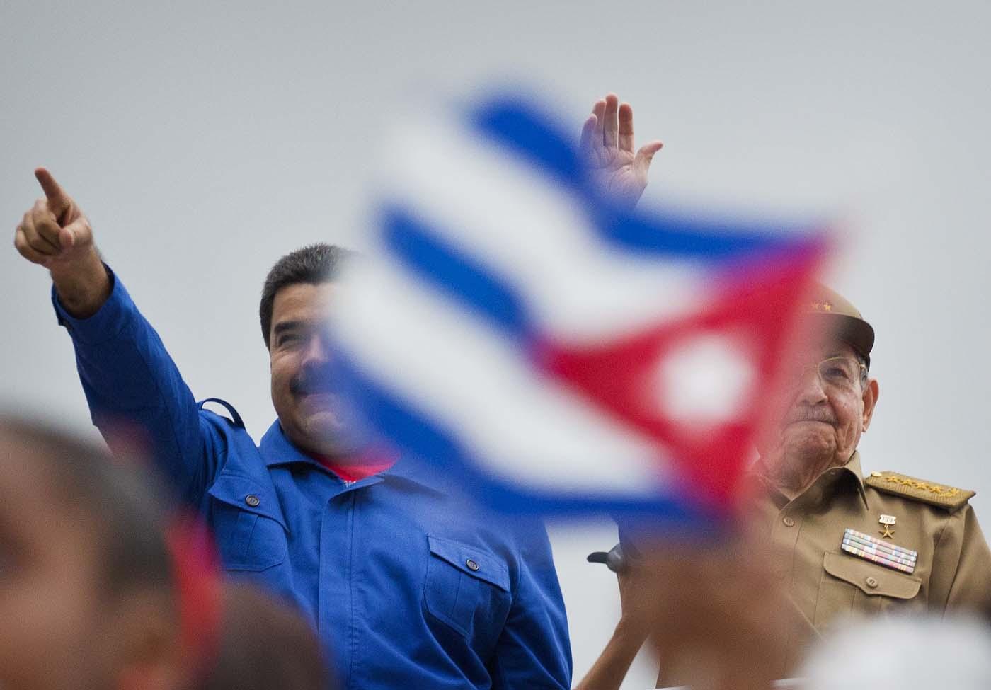 El presidente de Venezuela Nicolás Maduro, izquierda, y el presidente de Cuba Raúl Castro, saludan a marchistas mientras desfilan por la Plaza de la Revolución para festejar el 1 de mayo de 2015 en La Habana, Cuba. Miles de personas se reunieron en la plaza para la marcha tradicional, dirigida este año por los dos líderes. (Foto AP/Ramón Espinosa, Archivo)