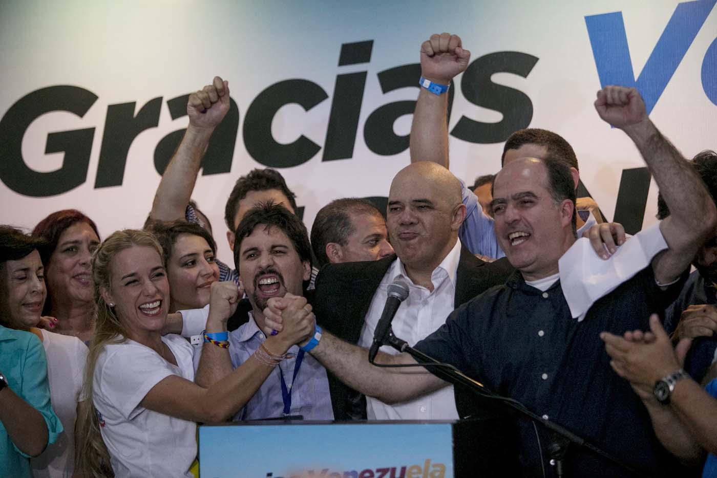 Los líderes opositores de izquierda a derecha Lilian Tintori, esposa del encarcelado  líder Leopoldo Lopez;  Freddy Guevara, del partido Voluntad Popular, y Jesús Torrealba, líder del Movimiento de Unidad Democratica, y el diputado electo Julio Borges celebran en Caracas, Venezuela, el lunes 7 de diciembre de 2015. La oposición venezolana tomará el control del órgano legislativo tras el resultado de los comicios del domingo 6 de diciembre(AP Photo/Alejandro Cegarra)
