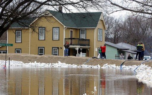 Personas permanecen cerca de un dique de reciente construcción que contiene el aumento del nivel de las aguas del río Mississippi en la localidad de Kimmswick, Missouri, el jueves 31 de diciembre de 2015. Las inundaciones comenzaron a bajar en diversas comunidades afectadas en el centro norte del país, donde centenares de viviendas registraron daños y centenares más fueron evacuadas. (Vía AP Foto/Laurie Skrivan/St. Louis Post-Dispatch)