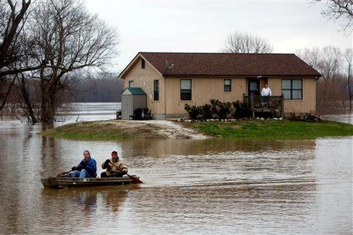 Scott Fox, al frente, decidió que era hora de dejar su residencia en Mississippi Boulevard, rodeada por el agua, y rema con su amigo Tony Watkins en Kimmswick, Missouri, el jueves 31 de diciembre de 2015. (Laurie Skrivan/St. Louis Post-Dispatch via AP)