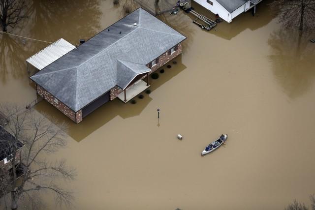En esta fotografía aérea, algunas personas se transportan en canoa en una calle inundada, el jueves 31 de diciembre de 2015, en Arnold, Missouri. El desborde de algunos ríos de la región centro-norte de Estados Unidos obligó a evacuar a cientos de personas, amenazó decenas de diques y prácticamente paralizó el transporte por automóvil, bote y tren en la zona metropolitana de St. Louis. (Foto AP/Jeff Roberson)
